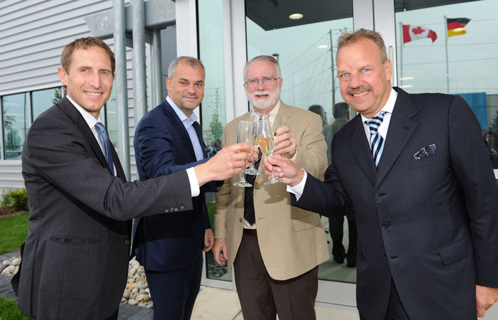 Carsten Kulcke, Darryl King, Doug Craig and Dieter Morszeck, CEO of Rimowa, toast after the ribbon cutting.