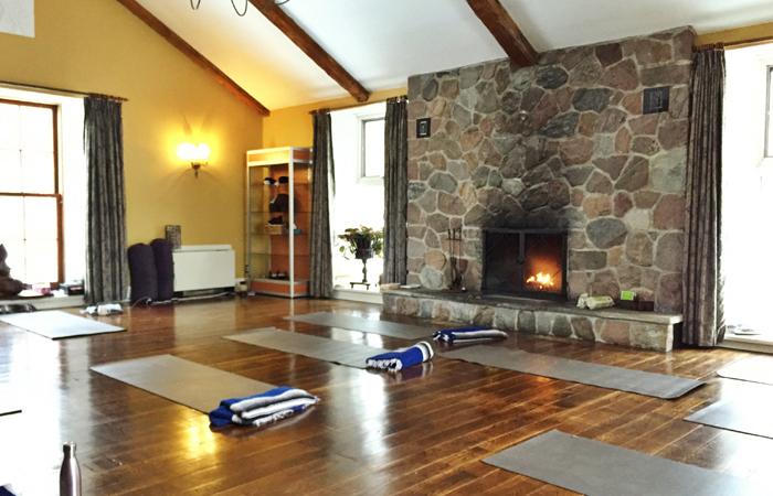 The cozy yoga studio has a fireplace.